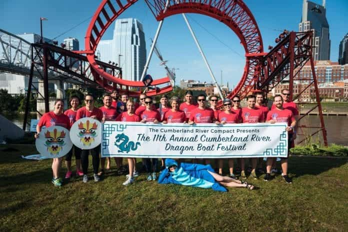 Massey 2017 Dragon Boat race team posing in front of a rollercoaster, holding a banner for the event.