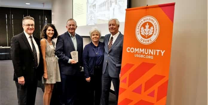 President Bob Fisher, with Judy Fisher and attendants at the USGBC Awards Ceremony, standing next to a USGBC banner
