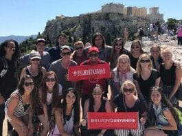 """students posing in front of mountain, holding signs that read """"from here to anywhere"""" and """"#BUabroad"""""""