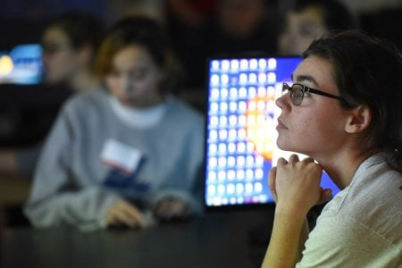 A student watches a presentation at the Women in Science Symposium