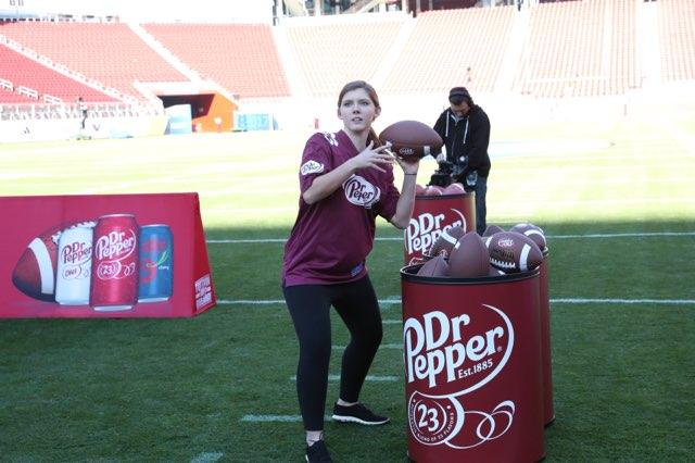 Sarah Thompson, wearing a Dr. Pepper football jersey, preparing to throw a football