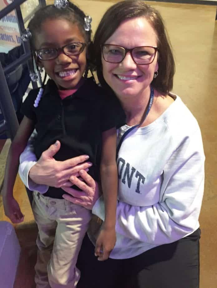 Joy Kimmons smiling with young student