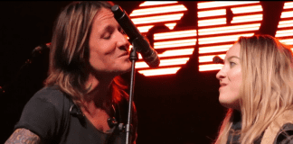 Ashley Sorenson sings into microphone with Keith Urban