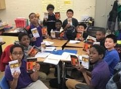 A group of students stitting at a table, posing with their books