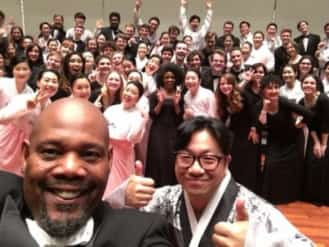 Ames (left) and Park (right) pose for a photo in front of members of both their choirs