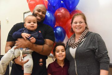 Family standing in front of balloons, smiling
