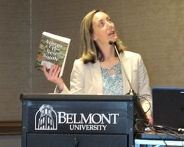 Dr. Mary Ellen Pethel, holding her book and looking up at a screen