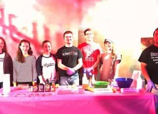 Students hosting the Adventure Science Center experience for children stand behind their experiment table