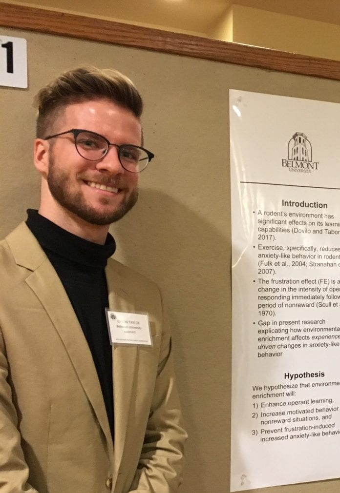 Student Eason Taylor poses in front of a poster at a research presentation.