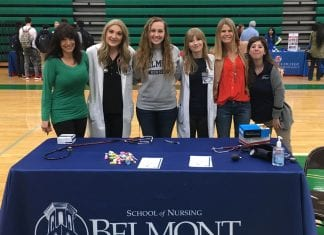Dr. Michaels and students standing behind their table at the Health Fair for local high school students.