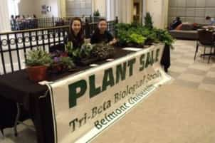 Students sit at a table during the Tri-Beta Plant sale