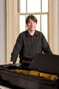Mark Volker standing behind a piano