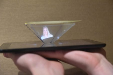 A student holds the hologram he made in his hand.