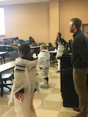 three fourth graders, wrapped in toilet paper, standing with a professor