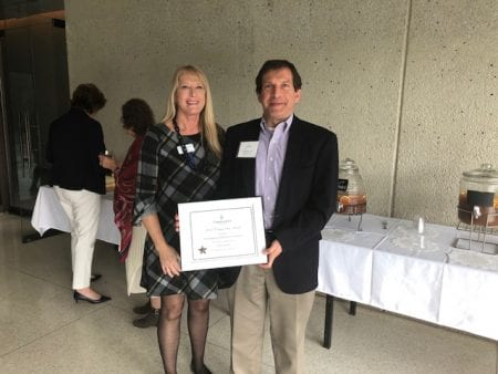 Tim Stewart accepts Belmont's award for the number of student community service hours