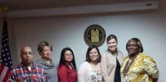 professors standing with HUD staff in the HUD office
