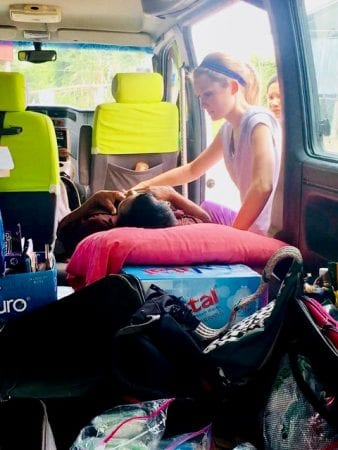 A FNP student examines a Cambodian patient in the back of her van -- getting creative with the resources she was given while on Maymester in Cambodia.