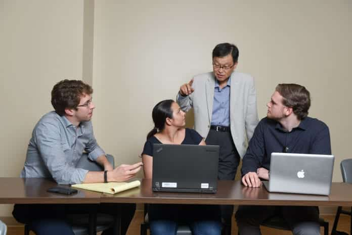 Students and faculty working around a laptop