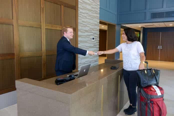 Two Students Shake Hands in Hotel Setting