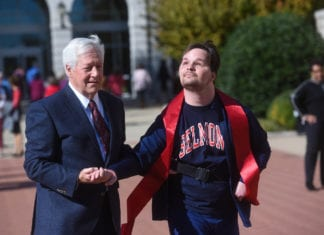 Luke Putney crosses the finish line of his marathon fundraiser on Belmont's campus with Dr. Fisher