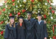 4 graduates in front of Christmas tree