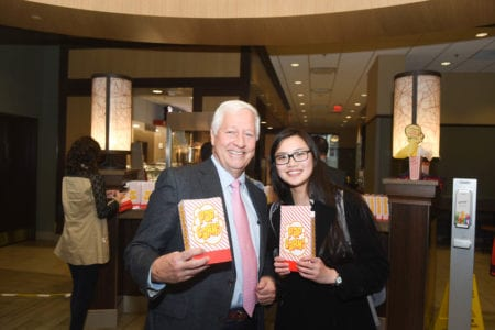 Dr. Fisher and Student hold popcorn boxes