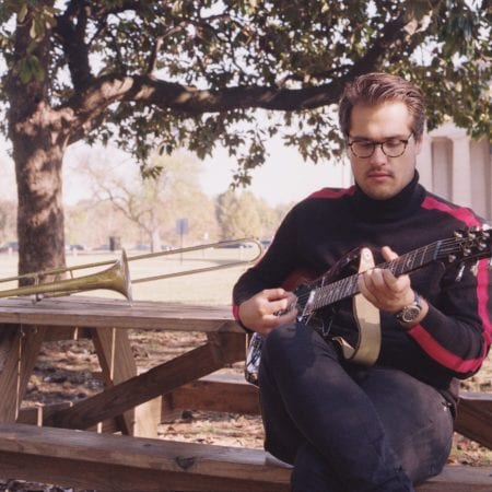Collin Felter playing guitar at the park