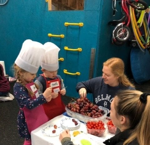 """OT students and cooking school friends making """"caterpillars"""" with grapes and tomatoes."""