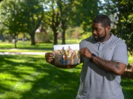 Carlos McDay admires photo from time in military on Belmont's campus
