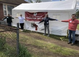 Volunteers stand at a distance in front of food distribution tent