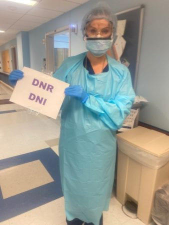 "Stahl in scrubs holding a sign that reads ""DNR DNI"""