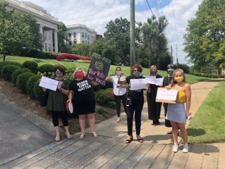 Belmont employees hold signs and bells