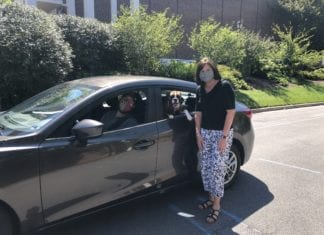 Powell stands with student veteran in a car