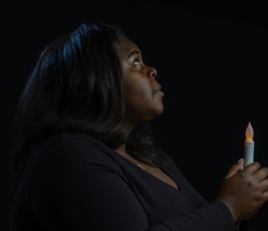 Student Holds Candle against dark background