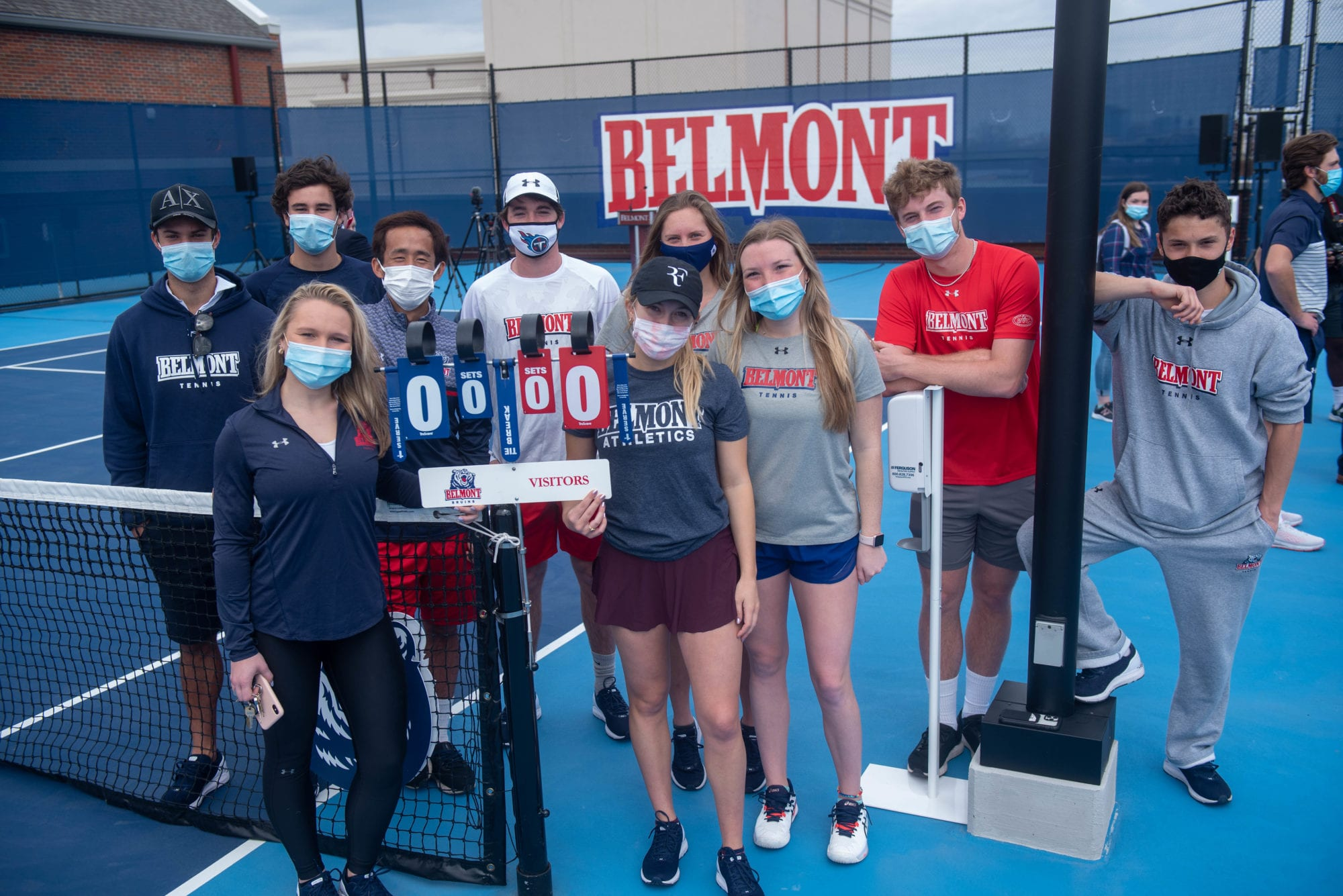 Tennis team members pose for a picture after a ribbon cutting ceremony opening Belmont's new rooftop tennis facility.