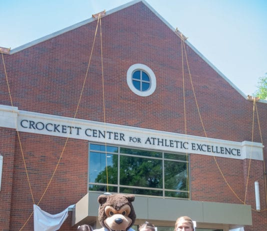 Cheerleaders and Bruiser mascot pose in front of new building