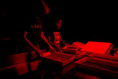 Students in Dark Room processing photographs