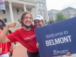 """two students hold """"welcome to Belmont"""" sign"""