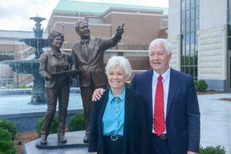 Judy and Bob Fisher stand in front of the sculpture presented in their honor