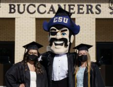 Two graduates from Charleston Southern University pose with Bucky before Commencement 2021