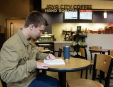 A student in Java City reading with a cup of coffee.