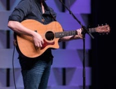 Andrew Peterson playing guitar during Chapel.
