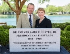 Dr. and Mrs. Hunter poses behind dedicated 34 years of leadership engraving