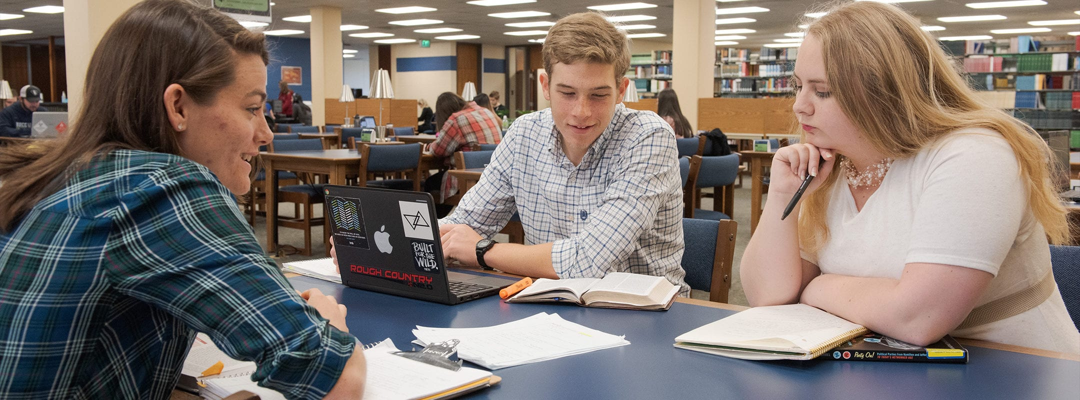 Three students in the CSU library studying together at a table.