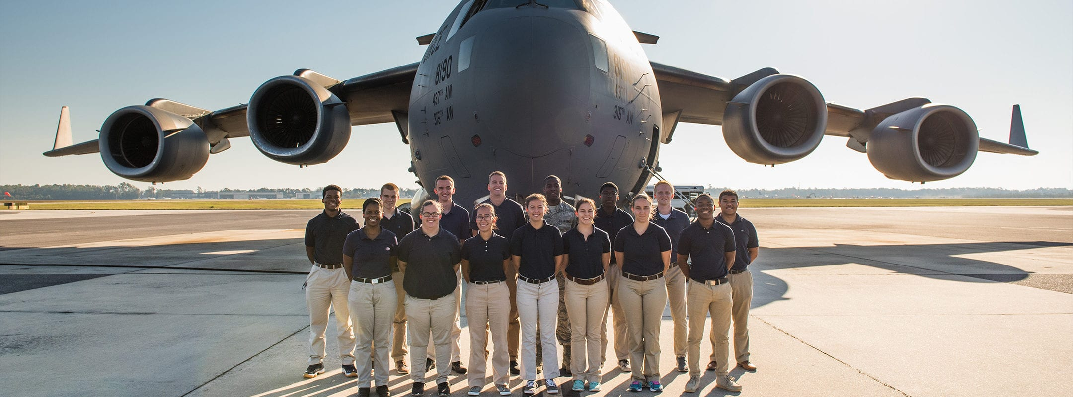 A group of students dressing in ROTC blue standing in front of a C17 plane.