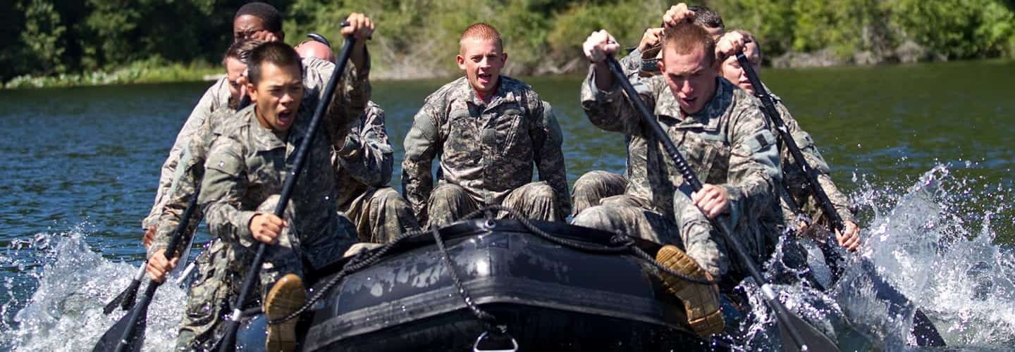Army cadets dress in fatigues rowing down a river in a raft.