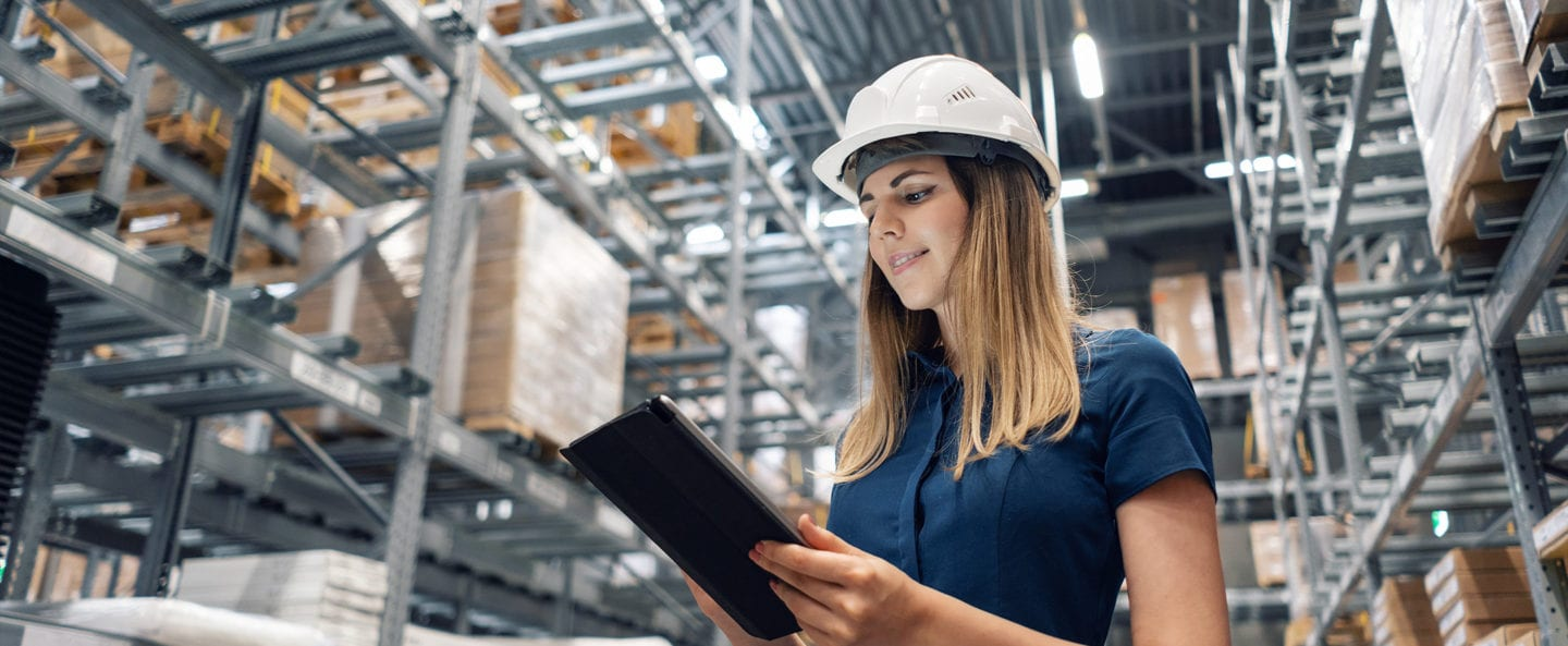 A young woman worker managing inventory inside a furniture manufcacturing warehouse.