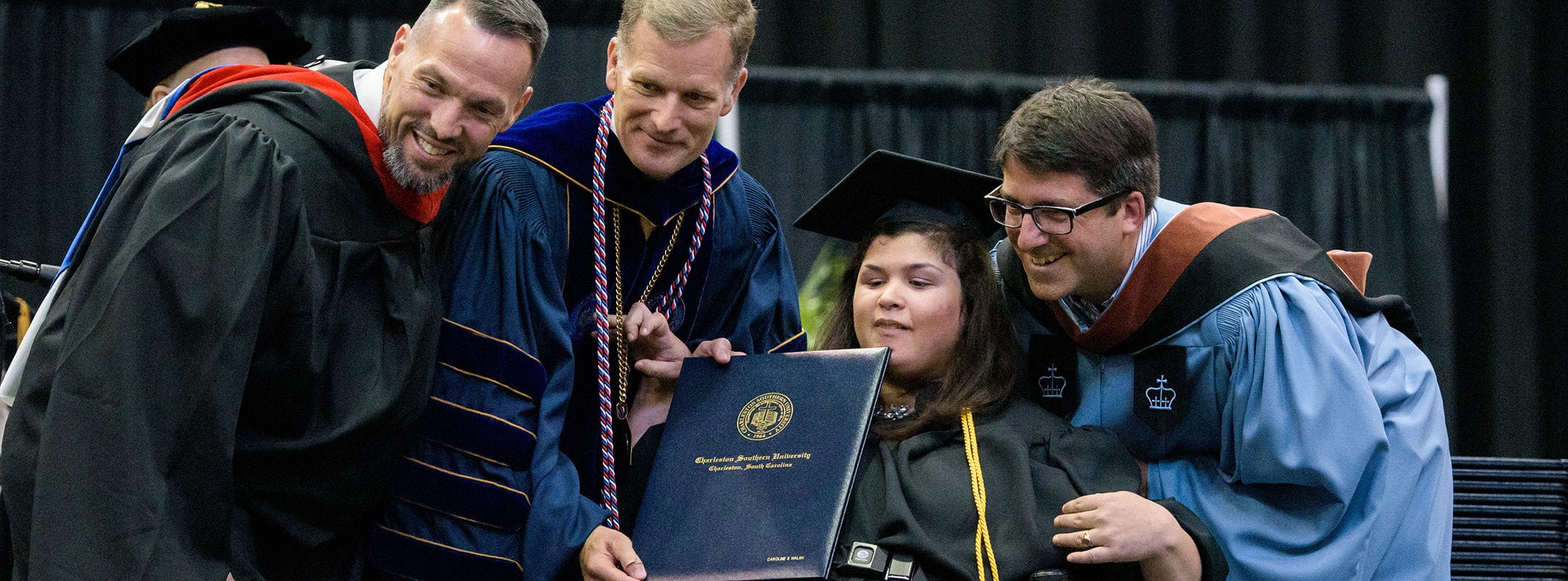 Student Caroline Walsh, in her wheelchair, receiving her diploma on stage at graduation with the CSU president and others.