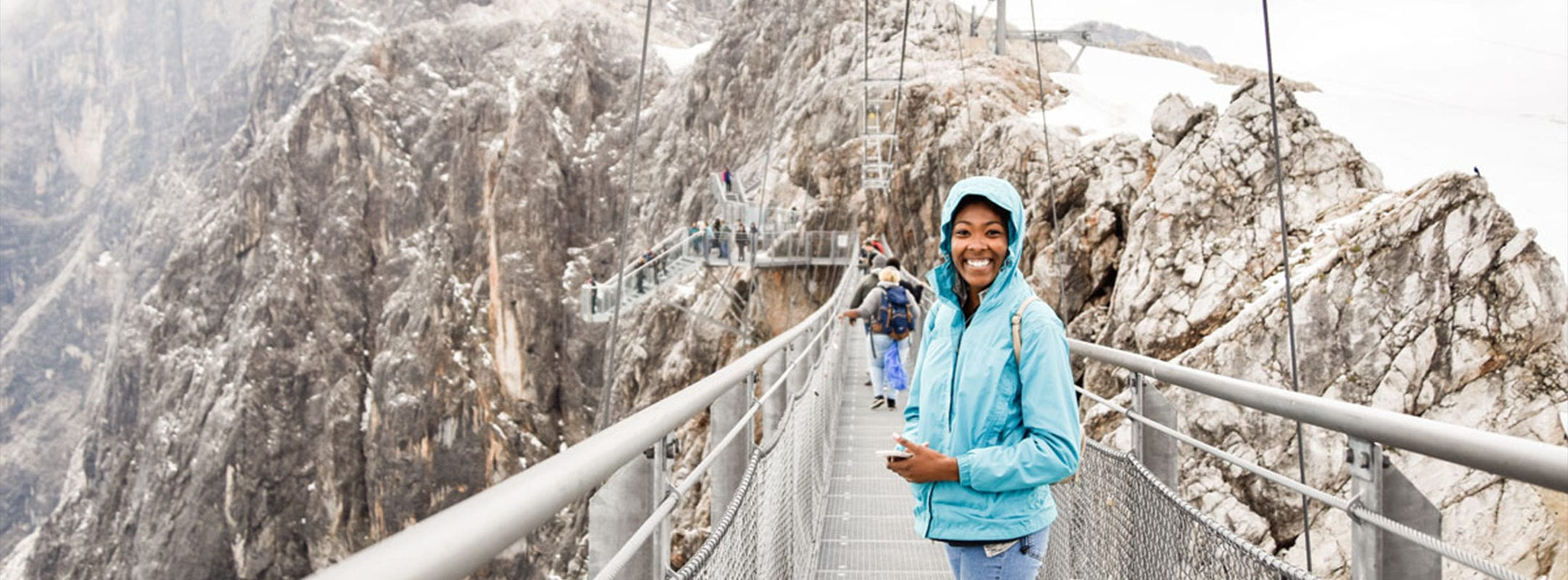 A student standing on a metal walkway bridge high up in mountains that are dusted in snow.