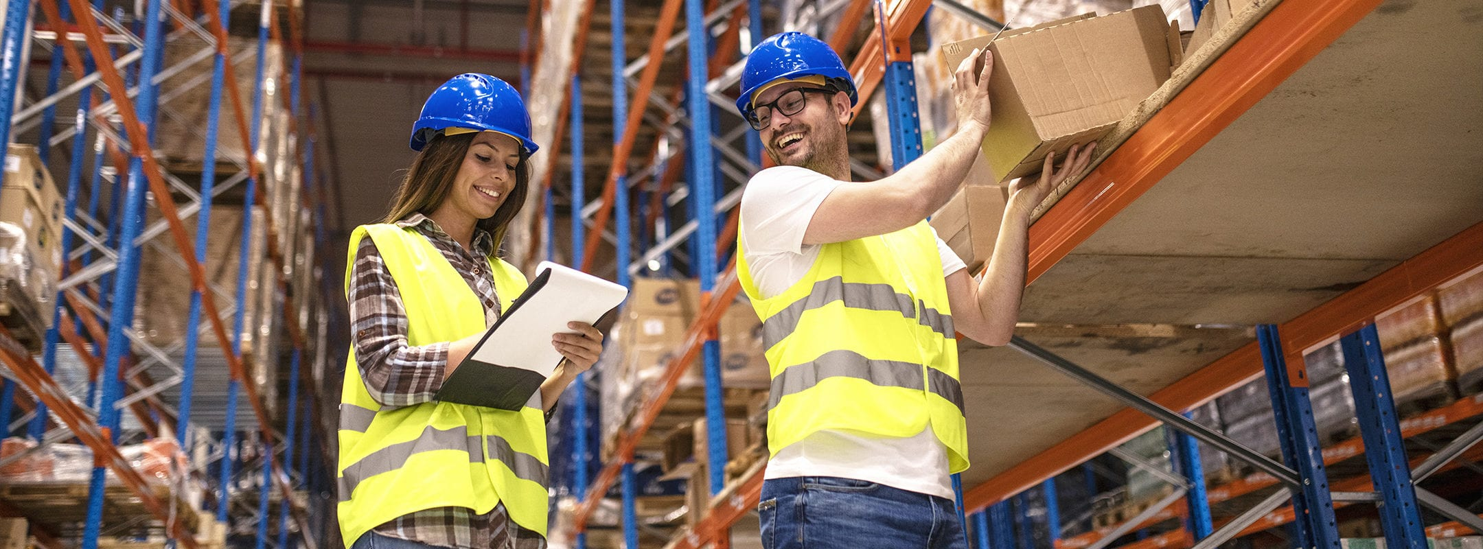 Two young people working together in warehouse storage facility. Checking goods at distribution warehouse.